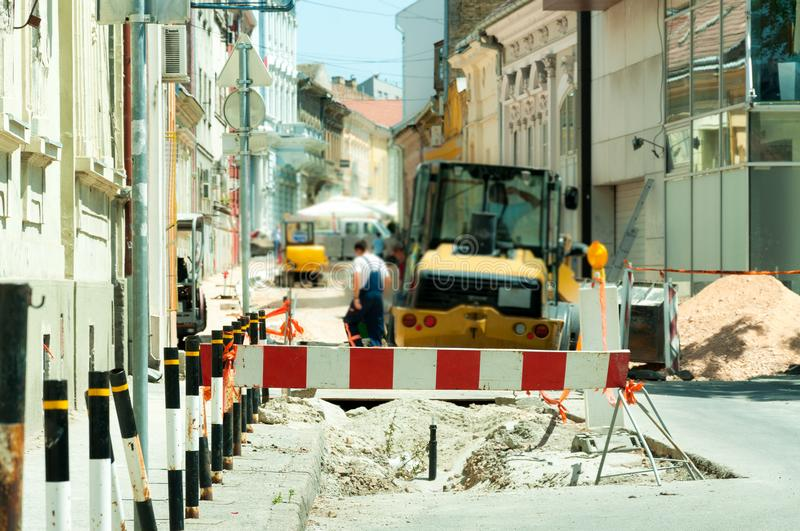 Work ahead street reconstruction site with sign and fence as road barricade. Work ahead street construction and reconstruction site with warning sign dead end royalty free stock image