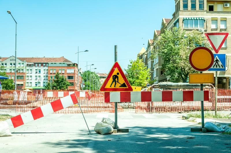 Work ahead street reconstruction site with sign and fence as road barricade. Work ahead street construction and reconstruction site with warning sign dead end stock images