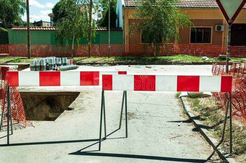 Work ahead street reconstruction site with sign and fence as road barricade. Work ahead street construction and reconstruction site with warning sign dead end stock photography