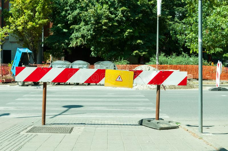 Work ahead street reconstruction site with sign and fence as road barricade. Work ahead street construction and reconstruction site with warning sign dead end stock image