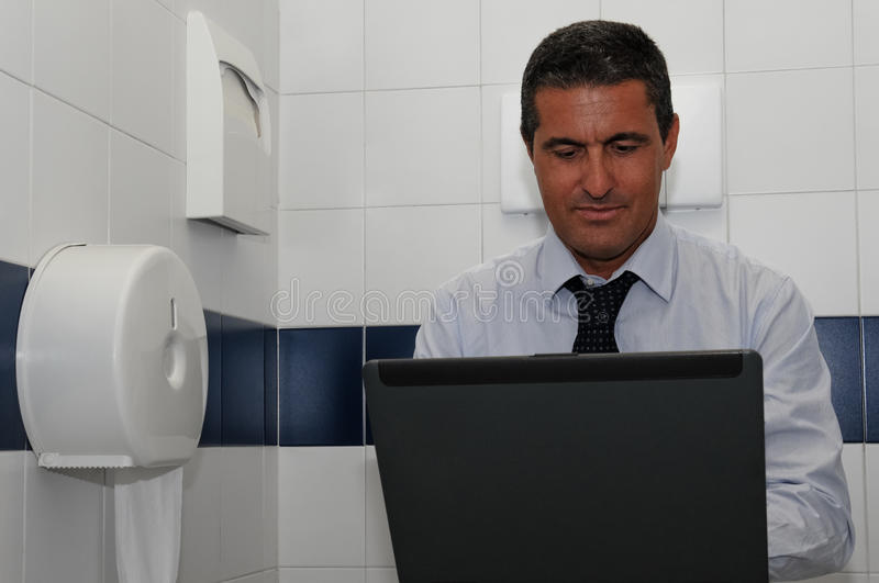 Work anywhere. Businessman to continue working you bring the laptop to the bathroom royalty free stock image