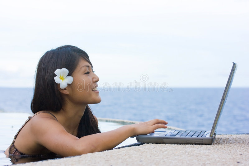 Work anywhere in paradise. Attractive young Asian business woman working remotely on a laptop computer beside an infinity pool at a private tropical resort stock photography