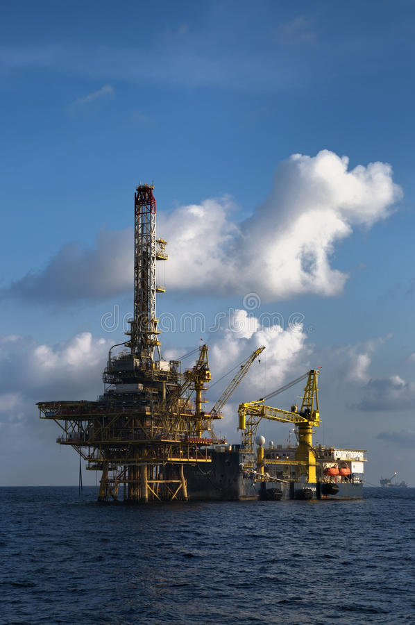 Work barge attached to oil platform at sea royalty free stock photography