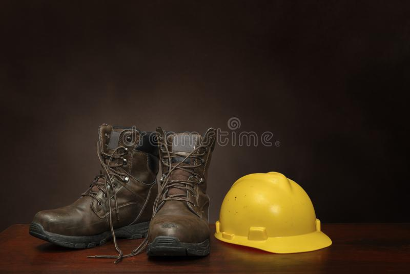 Work Boots and Construction Helmet On Brown With Copy Space. Horizontal shot of a pair of brown work boots and yellow construction helmet on a brown background stock image
