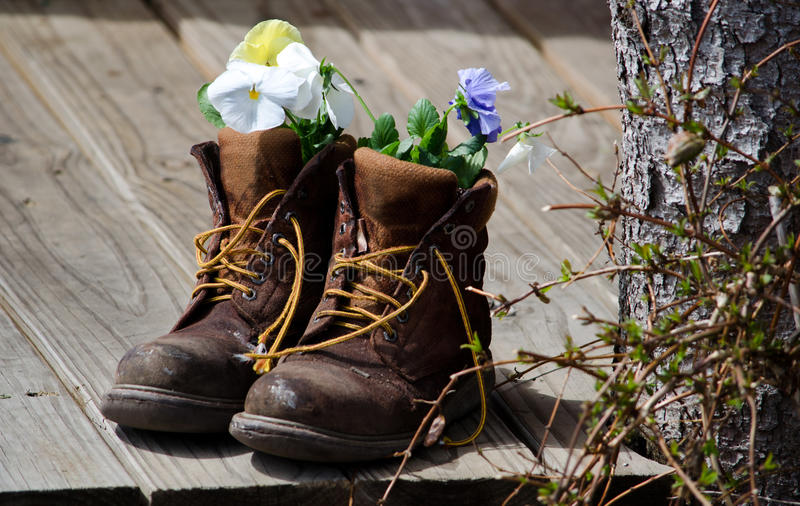 Work boots and flowers royalty free stock images