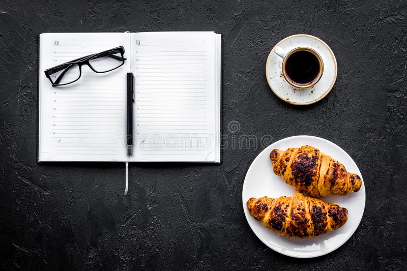 Work at breakfast. Coffee and croissants near notebook and glasses. Black background top view copyspace. Work at breakfast. Coffee and croissants near notebook royalty free stock images