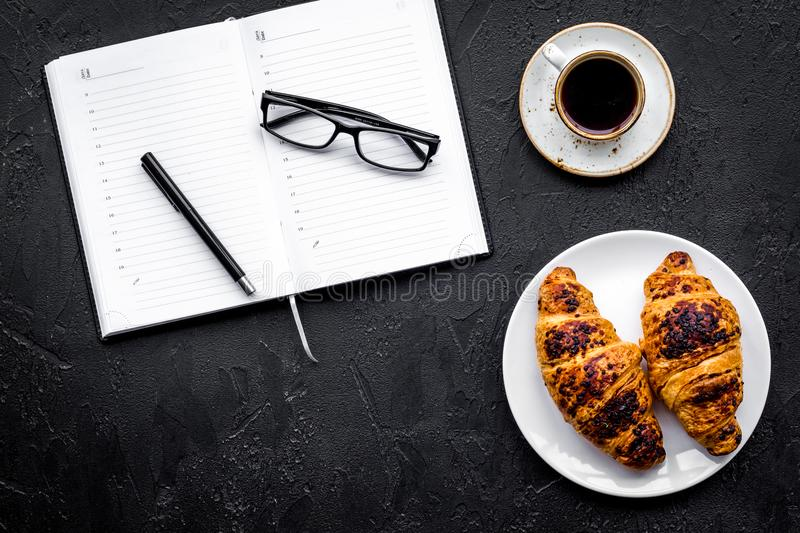 Work at breakfast. Coffee and croissants near notebook and glasses. Black background top view copy space. Work at breakfast. Coffee and croissants near notebook stock image