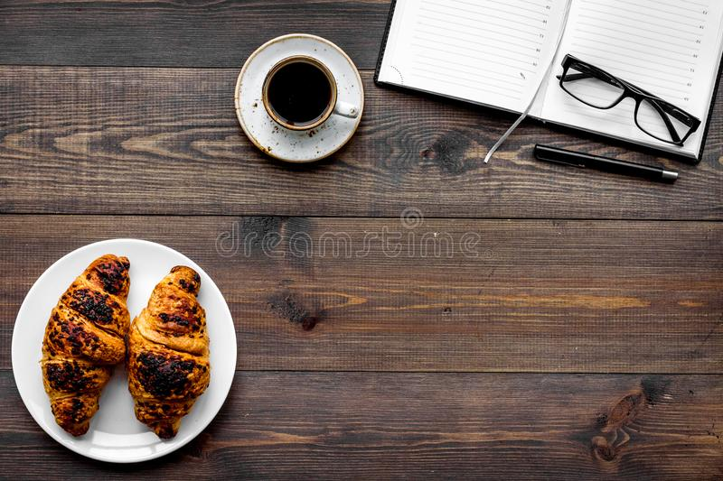 Work at breakfast. Coffee and croissants near notebook and glasses. Dark wooden background top view copy space. Work at breakfast. Coffee and croissants near stock image