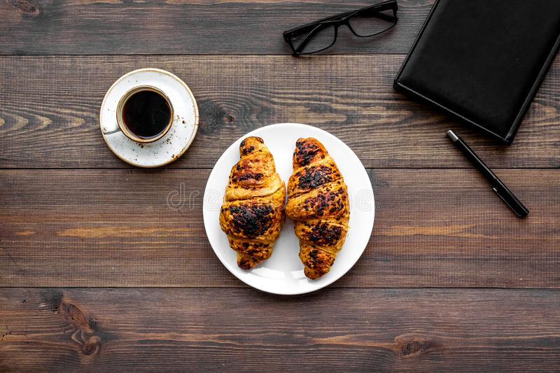 Work at breakfast. Coffee and croissants near notebook and glasses. Dark wooden background top view copy space. Work at breakfast. Coffee and croissants near stock images