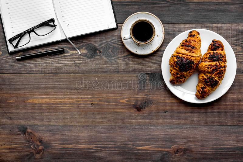 Work at breakfast. Coffee and croissants near notebook and glasses. Dark wooden background top view copy space. Work at breakfast. Coffee and croissants near royalty free stock photo