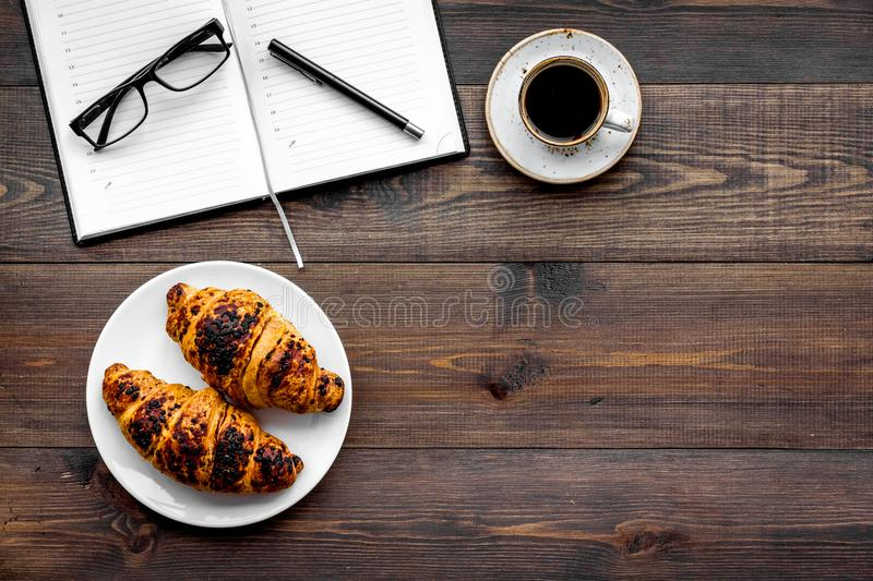 Work at breakfast. Coffee and croissants near notebook and glasses. Dark wooden background top view copy space. Work at breakfast. Coffee and croissants near royalty free stock photography