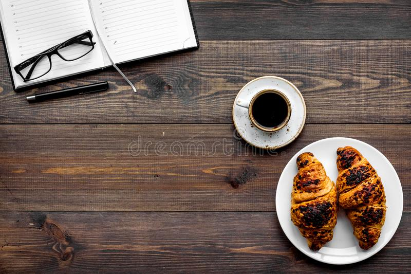 Work at breakfast. Coffee and croissants near notebook and glasses. Dark wooden background top view copy space. Work at breakfast. Coffee and croissants near stock photo