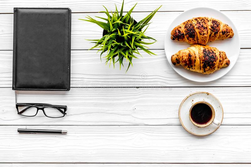 Work at breakfast. Coffee and croissants near notebook and glasses. White wooden background top view copy space. Work at breakfast. Coffee and croissants near stock images