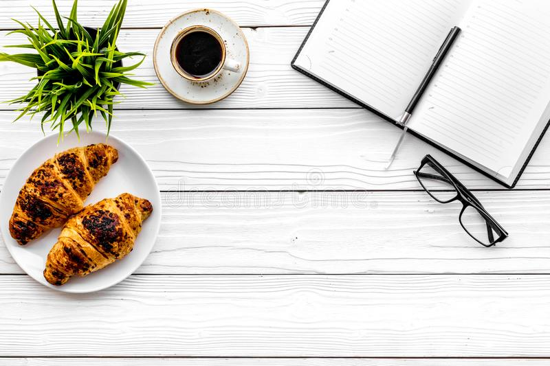Work at breakfast. Coffee and croissants near notebook and glasses. White wooden background top view copy space. Work at breakfast. Coffee and croissants near stock photography