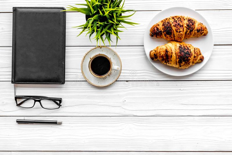 Work at breakfast. Coffee and croissants near notebook and glasses. White wooden background top view copy space. Work at breakfast. Coffee and croissants near stock photo