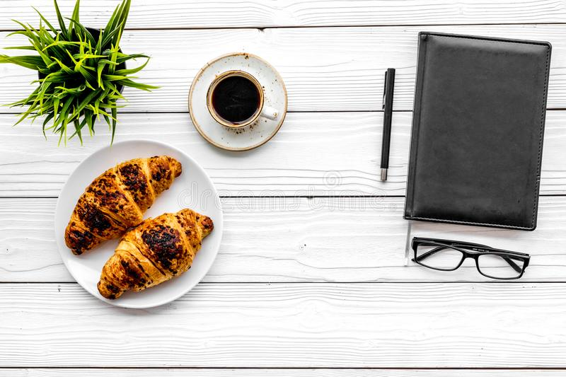 Work at breakfast. Coffee and croissants near notebook and glasses. White wooden background top view copy space. Work at breakfast. Coffee and croissants near royalty free stock photography