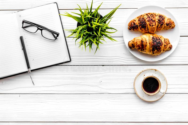 Work at breakfast. Coffee and croissants near notebook and glasses. White wooden background top view copy space. Work at breakfast. Coffee and croissants near royalty free stock images