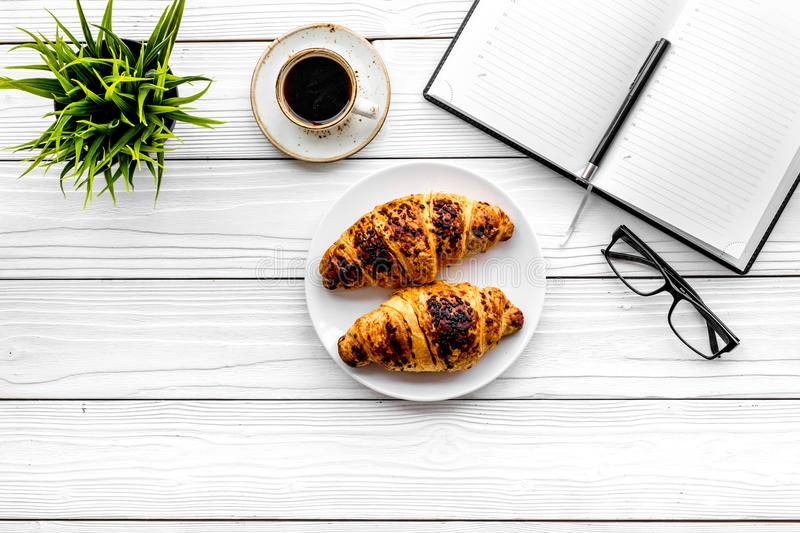 Work at breakfast. Coffee and croissants near notebook and glasses. White wooden background top view copy space. Work at breakfast. Coffee and croissants near stock photos