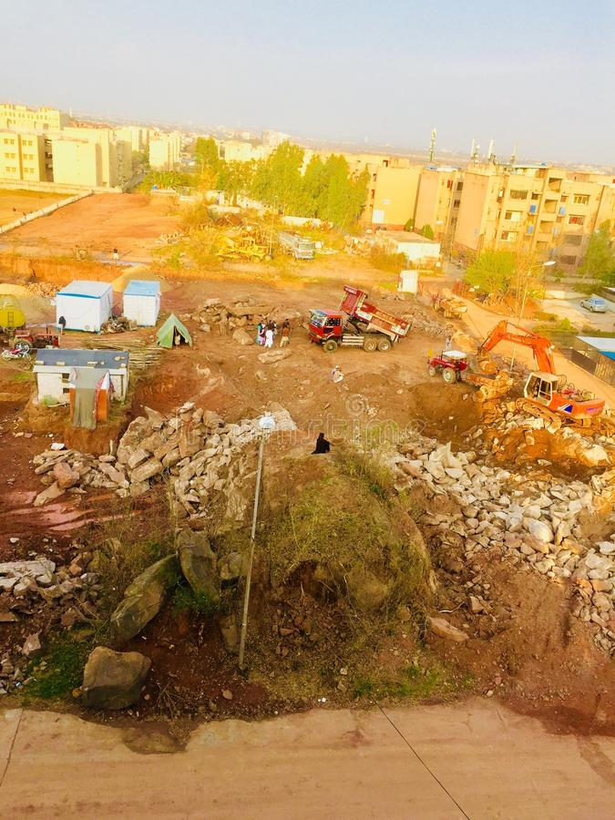 Construction work in process. Work for building apartments in process in beautiful city Islamabad Pakistan & x28; machine working,digging, stones, heavy stock photo