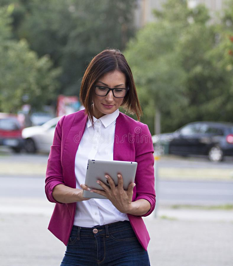 Work,business lady.She poses with her tablet.Town Novi Sad. Work.Young business lady. With short hair.Black Glasses.In a pink jacket and white shirt. She poses stock photo