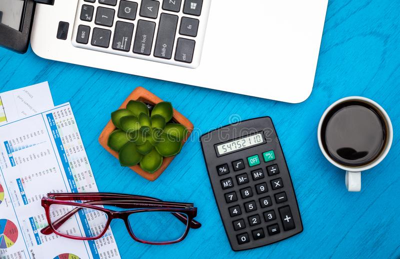 Work and business motivational concept with charts and graphs and calculator on wooden board. Investment Strategy motivational finance budget concept with charts royalty free stock photo