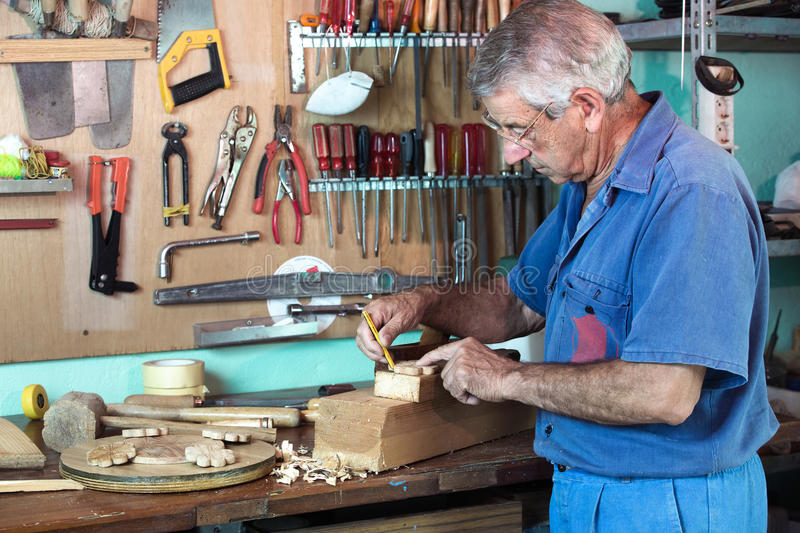 Work cabinetmaker marking handcrafted wooden pieces in garage at stock photos