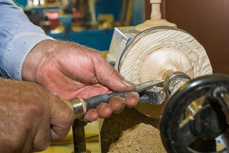 Work carpenter on a lathe on a tree. Close-up of a man`s hands with a chisel during the processing of a wooden blank.  stock photography