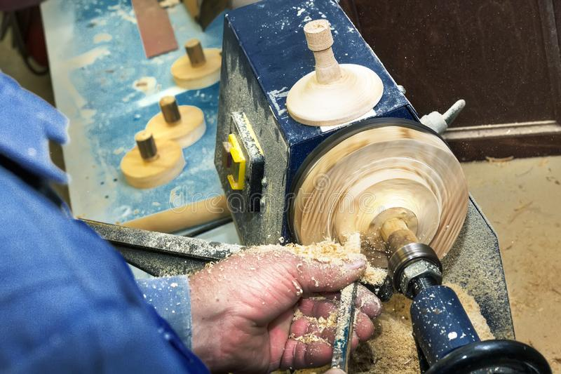 Work carpenter on a lathe on a tree. Close-up of a man`s hands with a chisel during the processing of a wooden blank.  stock image