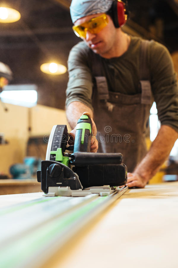 Work of carpenter. Man working with electric scroll-saw in workshop royalty free stock image