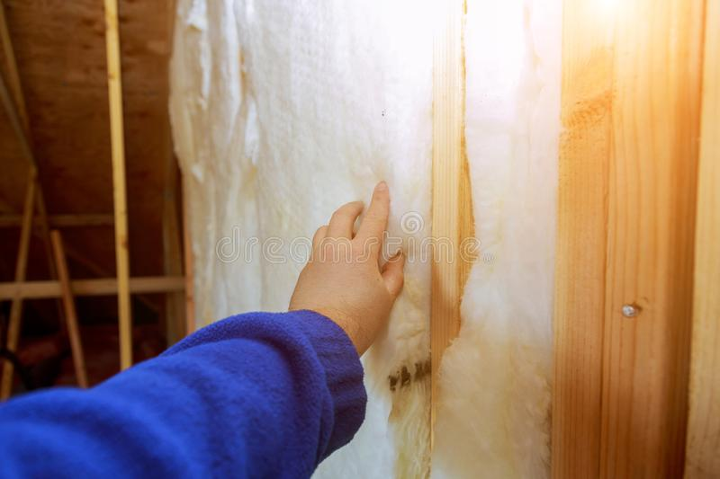 Work composed of mineral wool insulation in the wall heating insulation warm house. Insulation, a builder at work thermal glasswool fibreglass construction royalty free stock photography