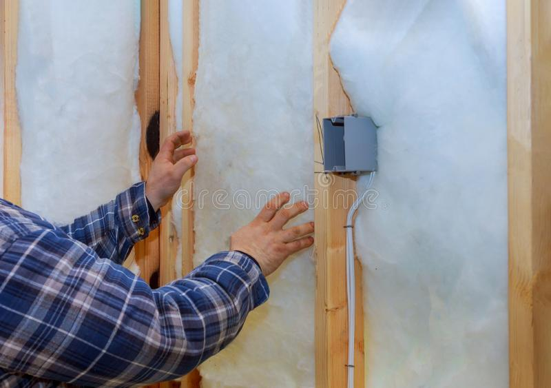 Work composed of mineral wool insulation in the wall heating insulation warm house. Insulation, a builder at work glasswool construction remodeling thermal royalty free stock photo