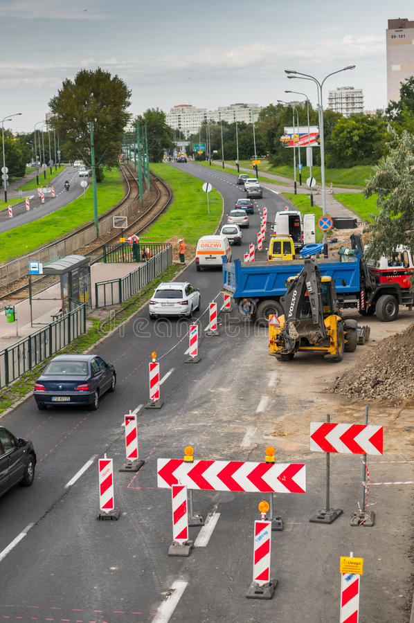 Work construction and driving cars. Driving cars along work constructions with excavator and truck close by apartment blocks on August 2017 in Poznan, Poland stock photography