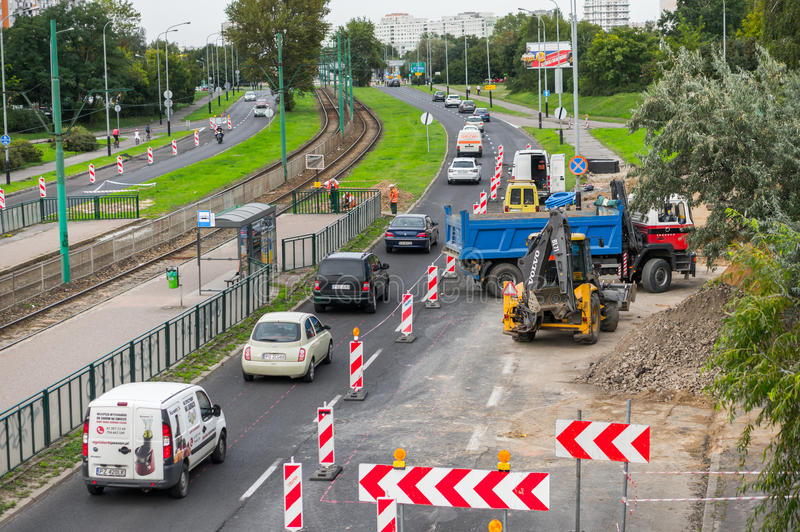 Work construction and driving cars. Driving cars along work constructions with excavator and truck close by apartment blocks on August 2017 in Poznan, Poland stock photo