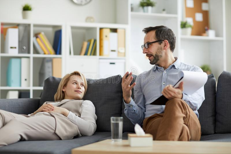 Work of counselor. Professional counselor sitting on couch next to his patient and giving advice about solving problem stock image