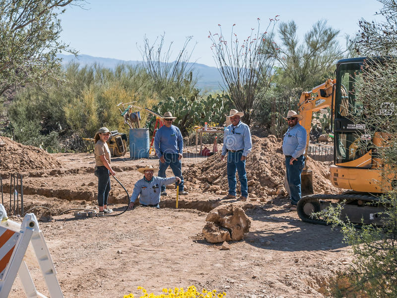 Work crew at the Arizona-Sonora Desert Museum, Tucson. Tucson, AZ, March 23, 2016: Blue-shirted work crew pauses to smile at a friend while digging a trench at stock photos