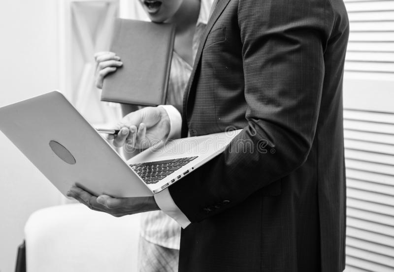 Work culture. Happy creative team working at office. Two joyful young people in formalwear holding laptop, book and stock photography