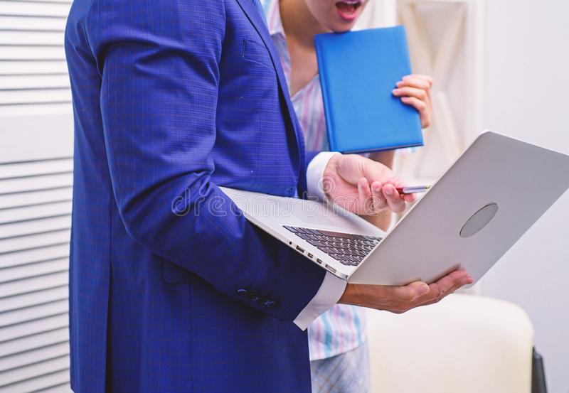 Work culture. Happy creative team working at office. Two joyful young people in formalwear holding laptop, book and stock photos