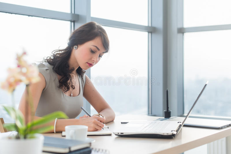 Work day of busy office manager, writing business plan in her notebook, working at work table. Work day of busy office manager, writing business plan in her stock photo