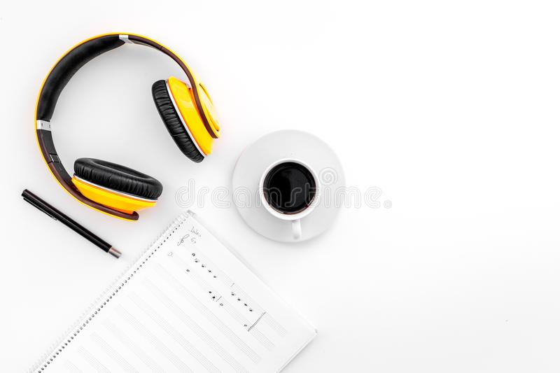 Work desk of modern composer. Music notes near headphones and coffee on white background top view copy space royalty free stock photo