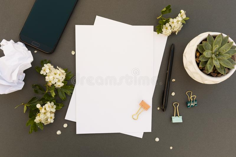 Work desk, table mock up with smartphone, blank pappers, spring flowers frame. Office work table. Copy space royalty free stock photos