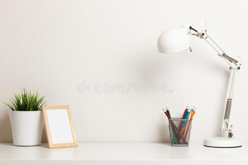 A work desk with a white lamp, a pencil stand, a frame and a home plant. The concept of modern space.  royalty free stock image