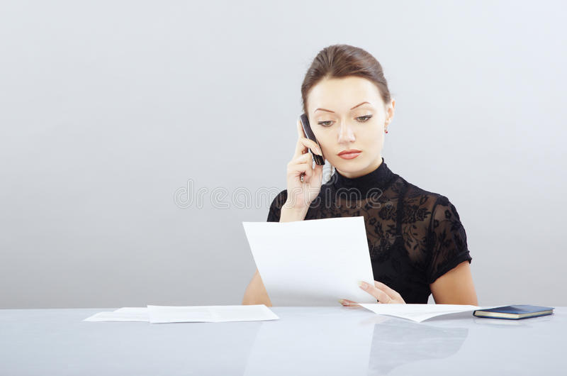 Work with documents. Young businesswoman working with documentation and calling phone royalty free stock images