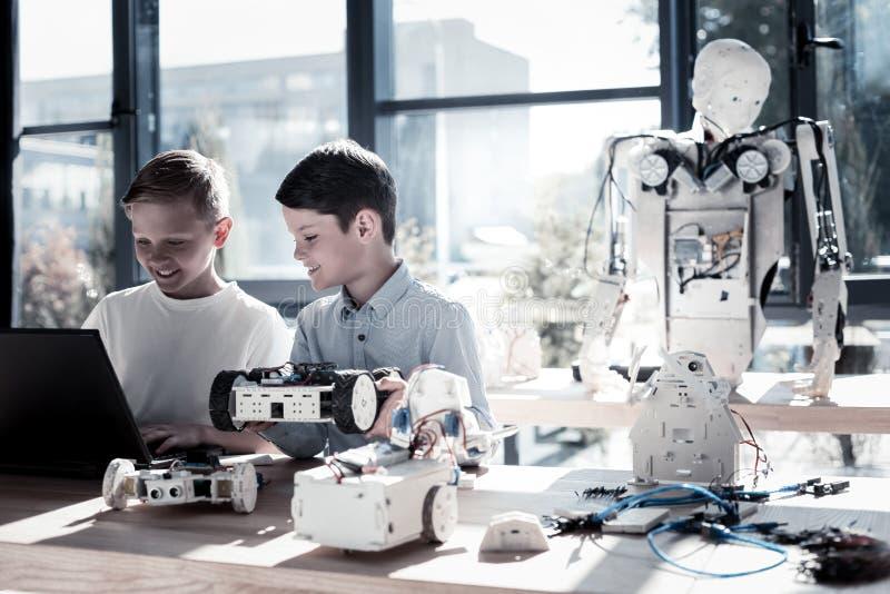 Joyful children working in workshop and programming robotic machines royalty free stock photos