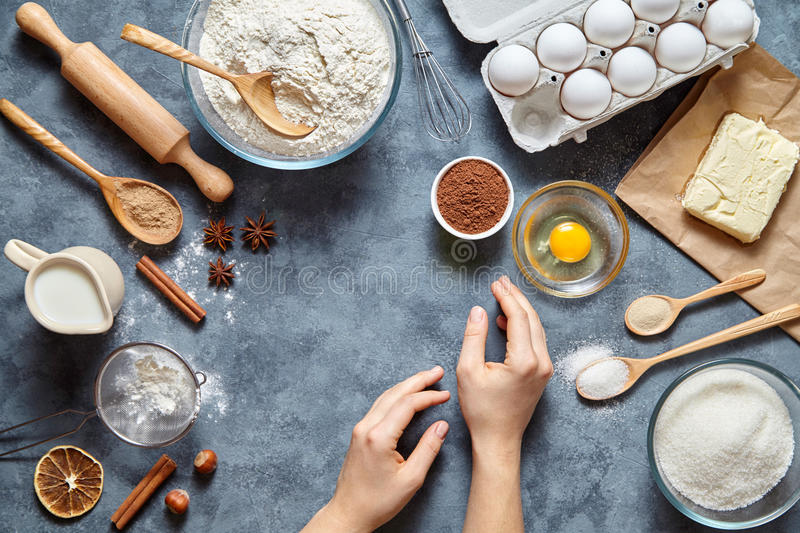Work with the dough. The kitchen table raw ingredients, the woman`s hand ready to knead the preparing ginger cake royalty free stock photos