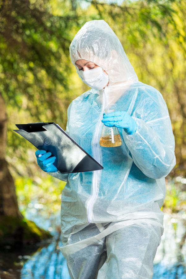 Work of an ecologist in nature, research of contaminated water. In a forest river royalty free stock images