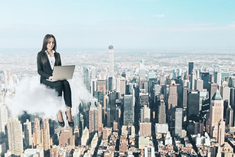 Work freedom and freelance concept. Attractive young businesswoman using laptop while sitting on cloud. City background. Work freedom and freelance concept stock images