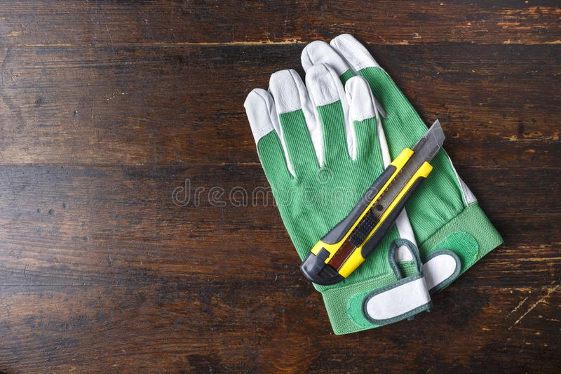 Work gloves and carpenter tools lie on a brown wooden table. View from above. space for text royalty free stock photos