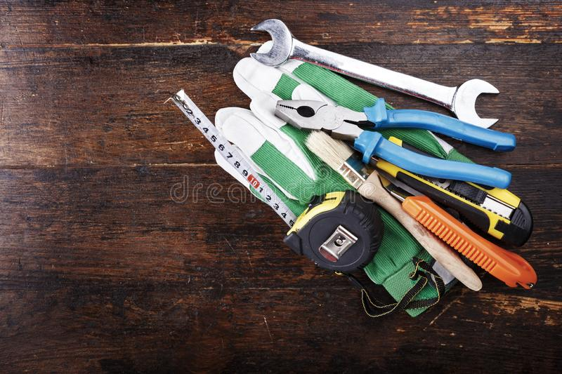 Work gloves and carpenter tools lie on a brown wooden table. View from above. space for text royalty free stock photography