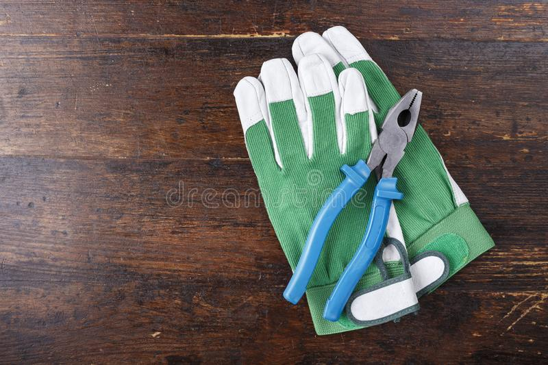 Work gloves and carpenter tools lie on a brown wooden table. View from above. space for text royalty free stock photo
