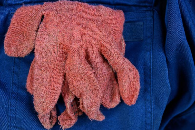 Work gloves in a pocket of crumpled fabric trousers. Red work gloves in a pocket of crumpled fabric trousers stock photo